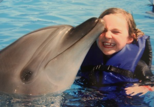 Neko gets a kiss from Andie the dolphin.