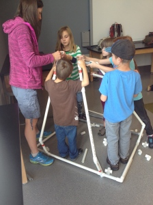 Junior architects building a wobbly tipi from PVC pipe at Telus Spark.